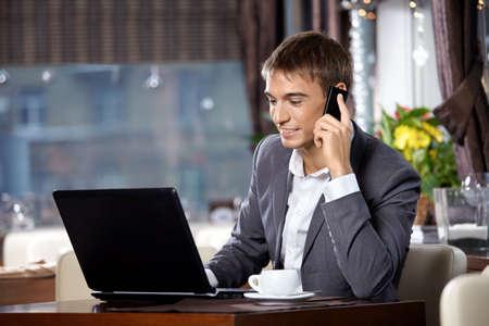 internet cafe: Hombre de negocios con el equipo port�til utiliza una comunicaci�n m�vil en caf� Foto de archivo