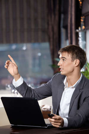 Business man with the laptop has raised a hand in cafe, calling up the waiter Stock Photo - 6328141