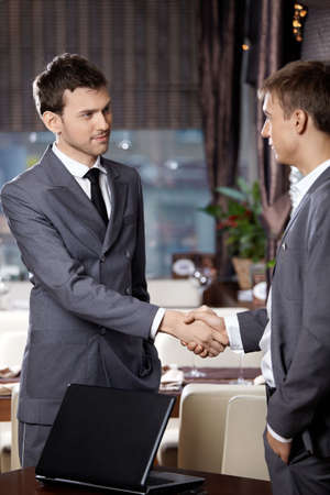Two business men shake hands each other at a meeting at restaurant photo