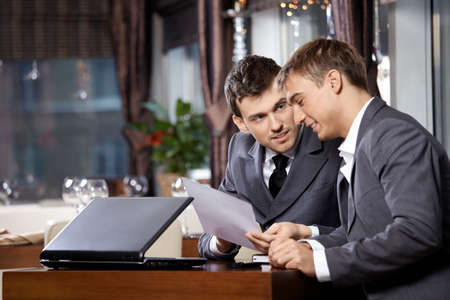 Two businessmen at restaurant discuss the document photo