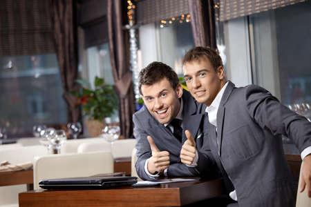 Two joyful businessmen at restaurant celebrate the transaction photo