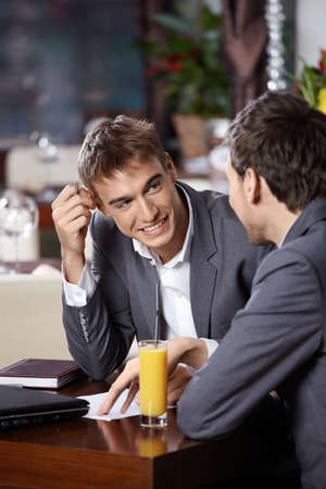 Two smiling business men have dinner at restaurant photo