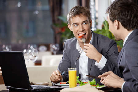 business activity: Two smiling business men eat at restaurant