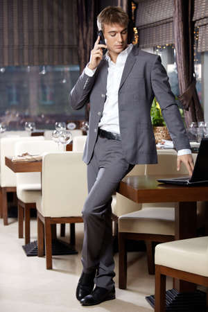 speaks: Attractive business man speaks by a mobile phone at restaurant