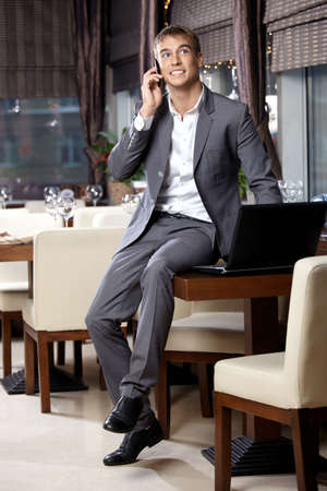 speaks: Happy business man speaks by a mobile phone at restaurant