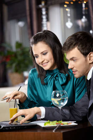 Young woman and the man discuss something on the laptop screen in cafe  photo