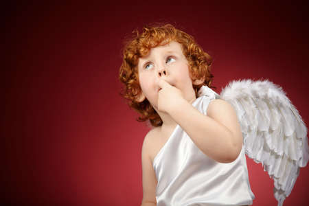 Portrait of the little boy with wings behind the back on a red background  photo