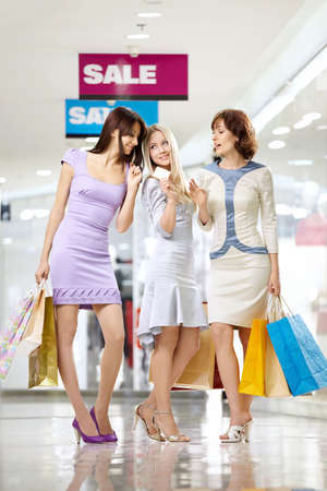 Three joyful girlfriends in shop with a credit card and bags photo