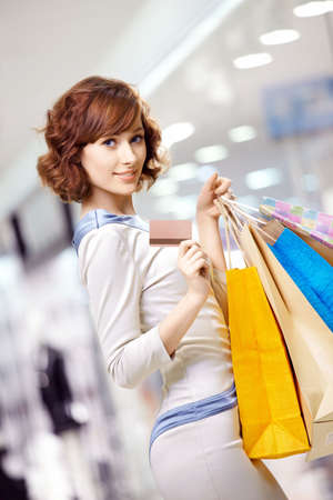Curly young woman in shop with a credit card photo