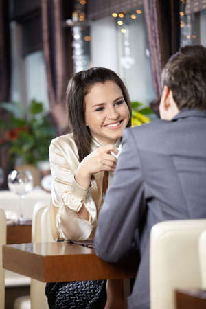 Two happy enamoured sit at restaurant