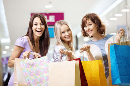 Happy smiling girls in shop with purchases photo