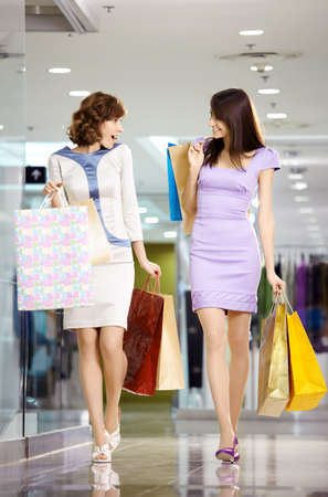 Two girl-friends on shopping walk on shopping centre with bags  photo