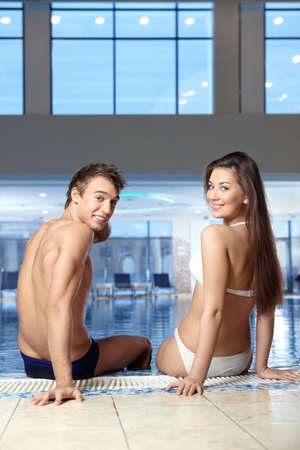 pool side: The couple sits on a pool side