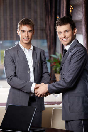Two smiling business men shake hands each other at a meeting at restaurant