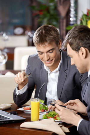 Two business men have dinner at restaurant photo