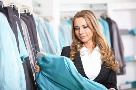 The attractive girl chooses clothes in shop photo