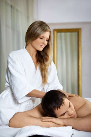 The girl does massage to the patient in spa salon photo