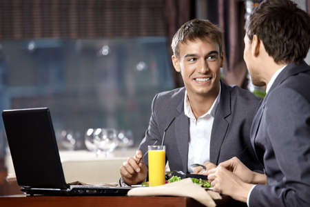 Two young businessmen have supper at restaurant  photo