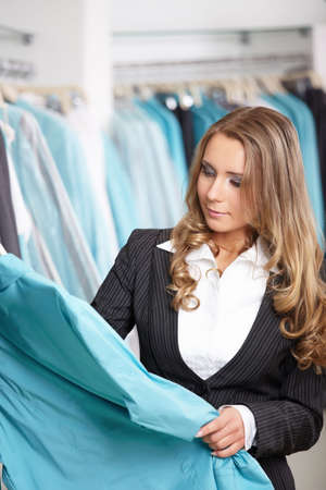 considers: The beautiful young girl considers clothes in shop Stock Photo