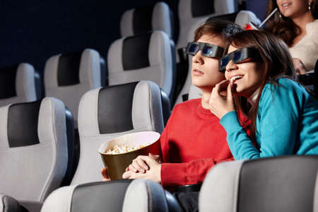 The couple with pop-corn looks cinema in 3d  photo