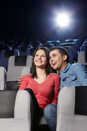 Enamoured laughing couple at a cinema on a forward background photo