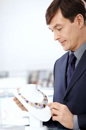 considers: The man in a suit considers a necklace in shop Stock Photo