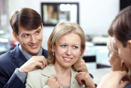 tries: The woman tries on a necklace at a mirror in shop Stock Photo