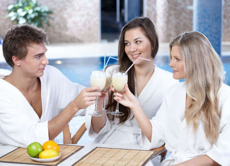 dressing gowns: Happy friends in white dressing gowns sit in cafe