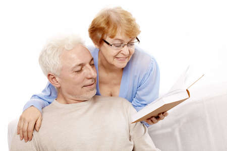 The elderly couple reads the book on a white background photo