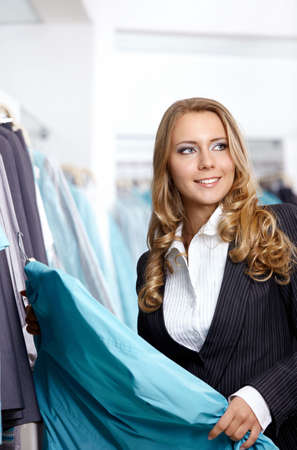 The beautiful girl in a suit chooses clothes photo