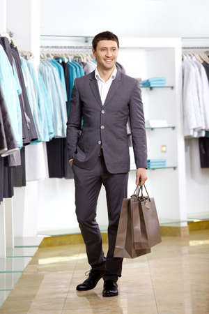 man shopping: The young man with a bag in shop Stock Photo