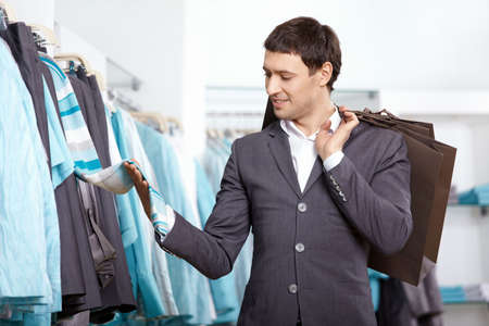 man shopping: The young man chooses clothes in shop