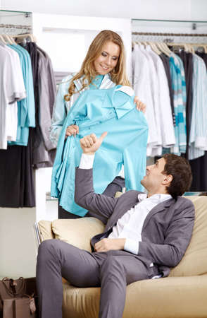 The wife consults on the husband about clothes purchase  photo