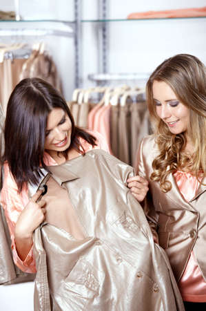 Two girls consider a shirt in shop photo