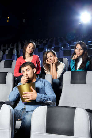 Enamoured girls admire the attractive man at cinema  photo