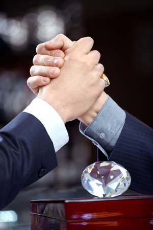 suit  cuff: Two struggling hands and brilliant on a forward background  Stock Photo