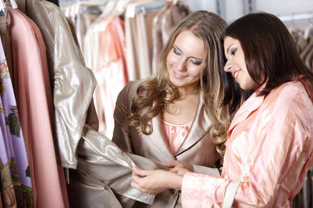 Two beautiful young girls choose clothes photo