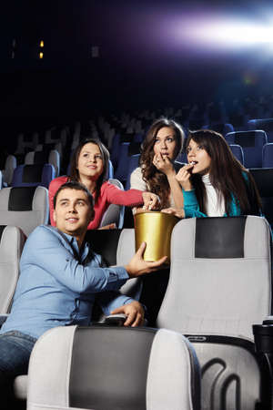 Young people at cinema eat pop-corn photo