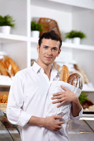 The young man with a package in a bakers shop photo