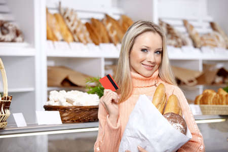 bagged: The beautiful girl with a credit card in shop Stock Photo