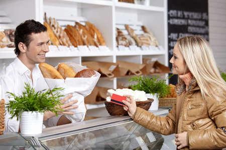 vendedores: La joven compra pan en tienda