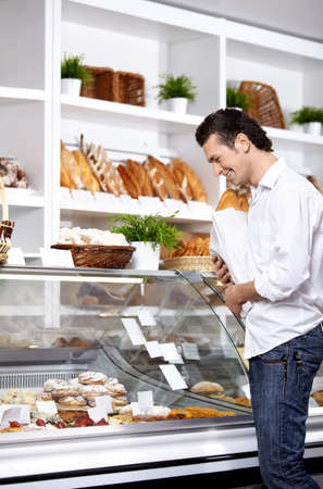 The young man buys bread in shop photo