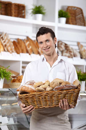 bread shop: The young man with a basket of rolls in shop