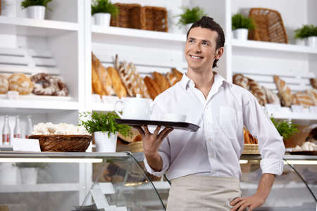 The young man with a tray on a forward background Stock Photo - 7636034