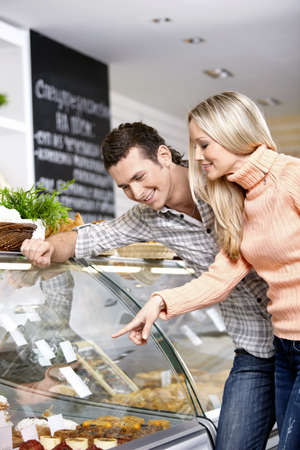 Young smiling couple at a shop show-window Stock Photo - 7636038