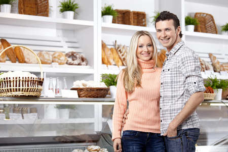 Happy young couple in a bakers shop photo