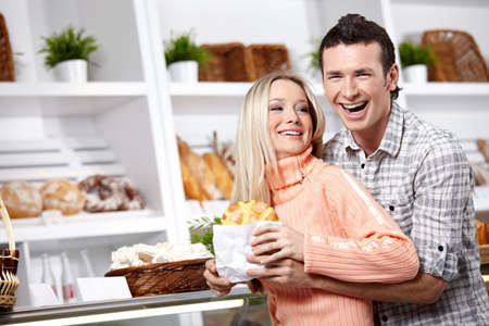 Embracing young couple in a bakers shop photo