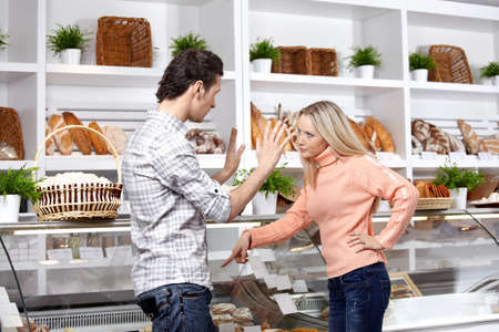 The young couple quarrels in a bakers shop photo