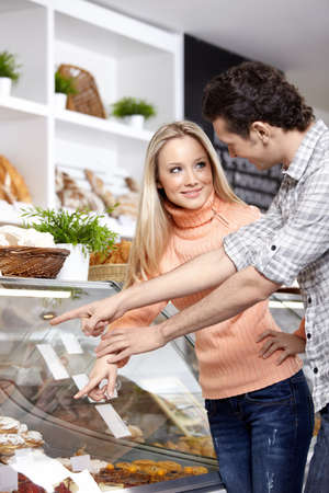 The young people buy bread in shop photo