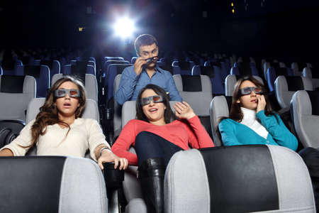 The young man observes of the attractive girl at cinema photo